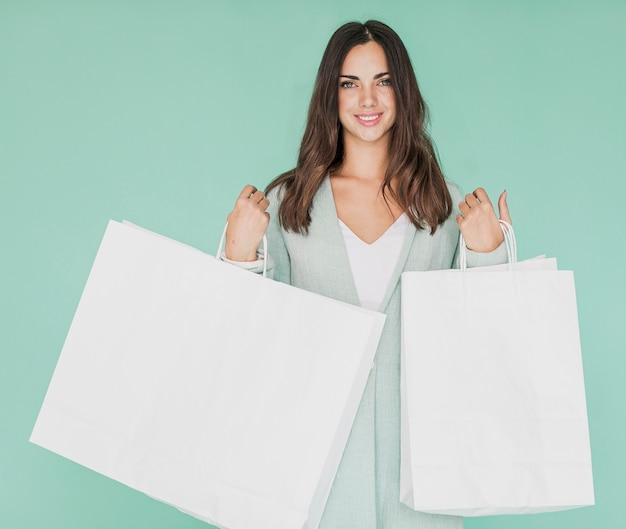 Kobieta z białym zakupy zarabia netto na błękitnym tle