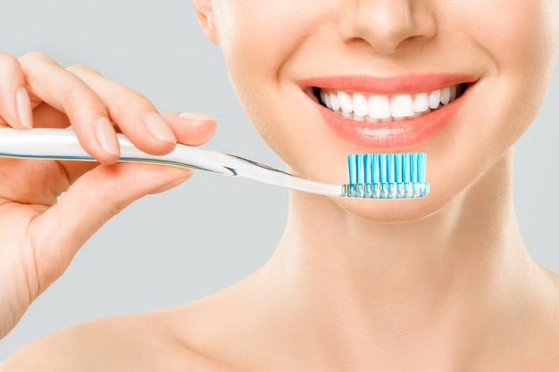 Kobieta z białymi zębami za pomocą szczoteczki do zębów