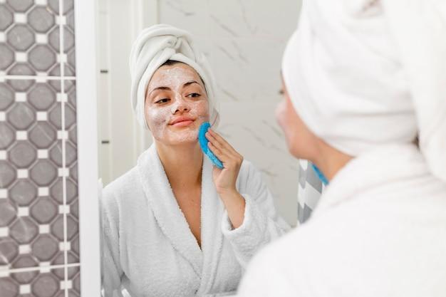 Kobieta z bliska czyszczenia twarzy