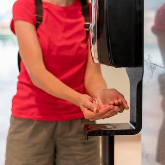 Kobieta z bliska przy użyciu środka dezynfekującego do rąk