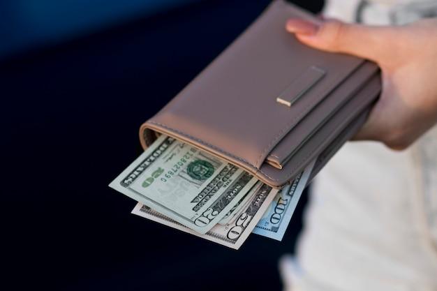 Kobieta z bliska trzyma czarną torebkę, w której leżą dolary