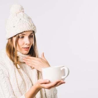 Kobieta z bólem gardła trzyma gorący napój