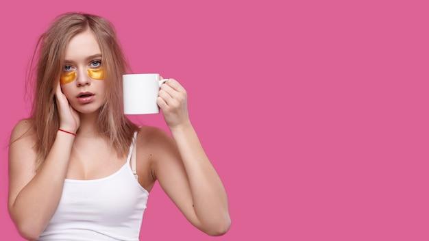 Kobieta z bólem głowy i kaca trzymając kubek z gorącym napojem na różowym na białym tle