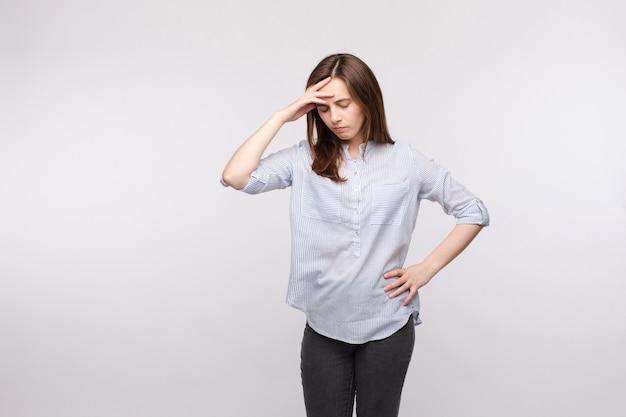 Kobieta z bólem głowy i zamkniętymi oczami.
