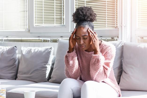 Kobieta z bólem głowy, siedząc na kanapie
