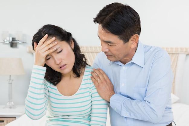 Kobieta z bólem głowy siedzi na łóżku z mężem obok niej