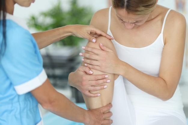 Kobieta z bólem nóg podczas wizyty u traumatologa ortopedycznego