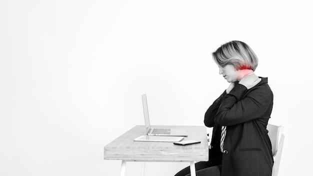 Kobieta z bólem szyi za pomocą laptopa