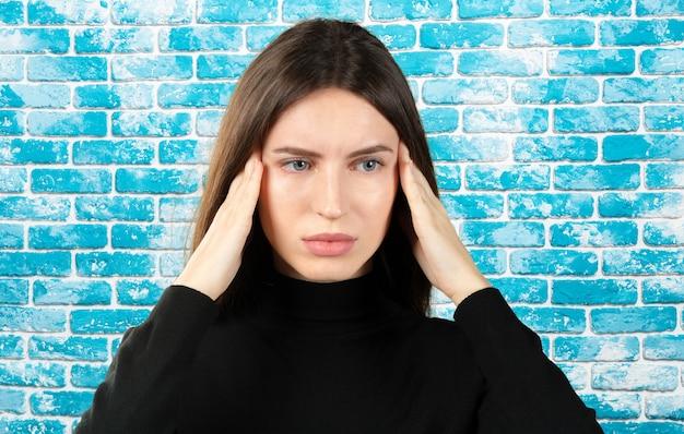 Kobieta z bólem w głowie trzyma migrenę