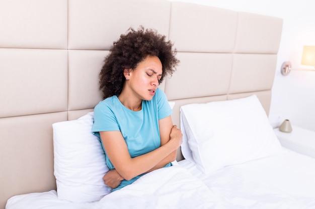 Kobieta z bolesnym wyrazem twarzy, trzymając się za ręce przed brzuchem cierpiącym na bóle menstruacyjne, smutno leżąc na łóżku w domu