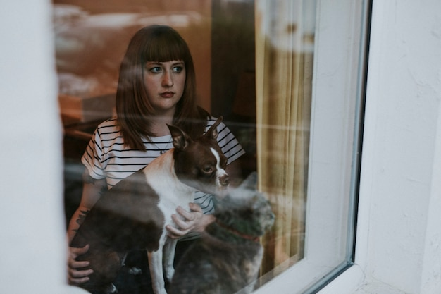 Kobieta z boston terrierem wyglądającym przez okno podczas izolacji społecznej spowodowanej pandemią covid-19 w wielkiej brytanii.