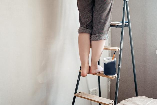 Kobieta z bosymi stopami poplamiona białą farbą stoi na drabinie
