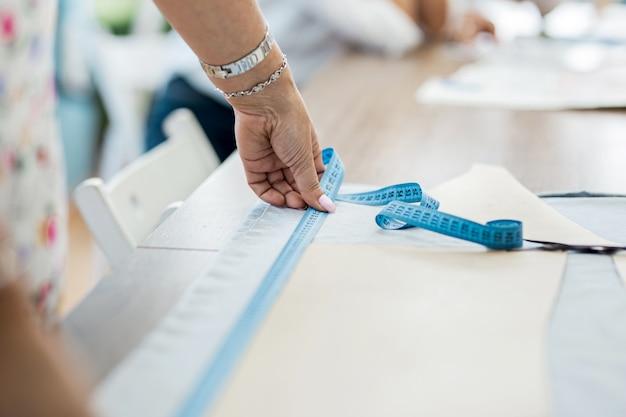 Kobieta z bransoletką mierzy tkaninę warsztaty krawieckie mody