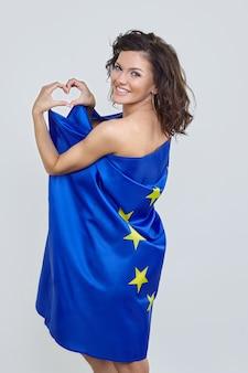 Kobieta z brązowymi włosami pozuje z flagą unii europejskiej.