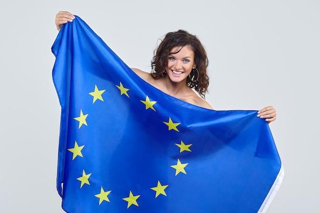 Kobieta z brązowymi włosami z flagą unii europejskiej w studio na białym tle