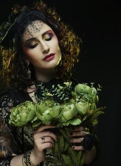Kobieta z brigt obliczem trzyma duże zielone kwiaty