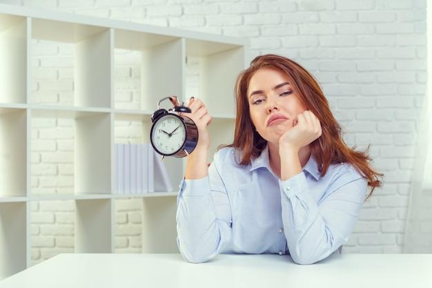 Kobieta z budzikiem przy stołem w biurze