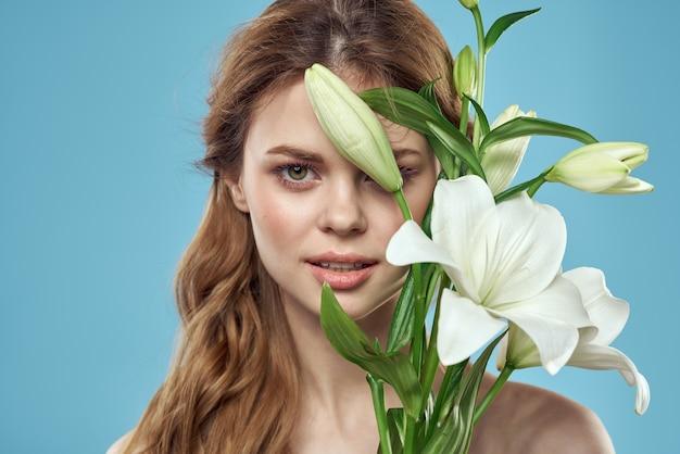 Kobieta z bukietem białych kwiatów na niebieskim tle nagie ramiona piękna twarz