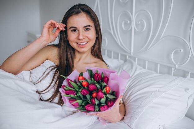 Kobieta z bukietem kwiaty w łóżku