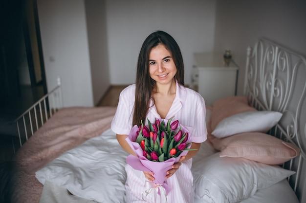 Kobieta z bukietem kwiaty w sypialni