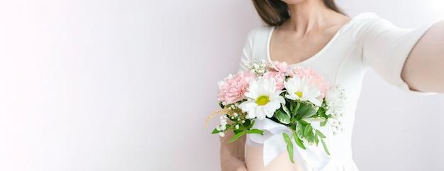Kobieta z bukietem ślubnych kwiatów i selfie na jasnym tle.