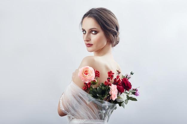 Kobieta z bukietem sztucznych kwiatów za nią. dziewczyna w jasnej przezroczystej sukience z odkrytymi plecami i kwiatami. artystyczny portret kobiety na okładkę książki