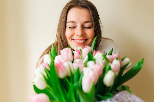 Kobieta z bukietem wiosennych kwiatów. szczęśliwa zaskoczona modelka zapachu kwiatów. dzień matki. wiosna