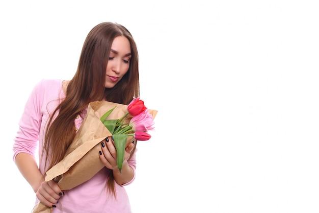 Kobieta z bukietem wiosennych kwiatów. szczęśliwa zdziwiona wzorcowa kobieta wącha kwiaty. dzień matki. wiosna. 8 marca. pojedynczo na białym.