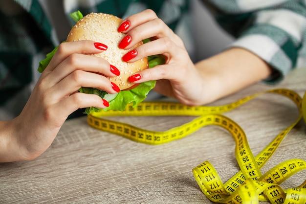 Kobieta z burger i miarkę podczas diety