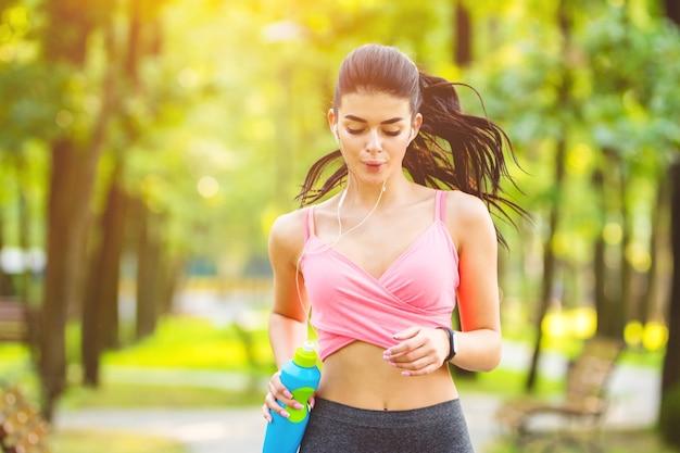 Kobieta z butelką biegająca w parku na słonecznym tle