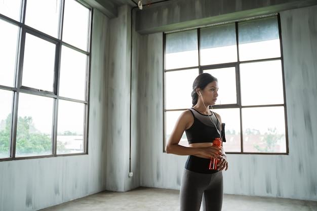 Kobieta z butelką do picia noszenia sportu zrobić sobie przerwę