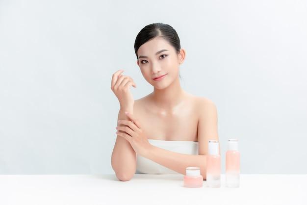 Kobieta z butelkami kosmetycznymi na stole