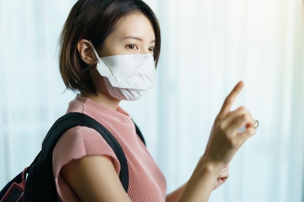 Kobieta z chirurgiczną maską i plecakiem
