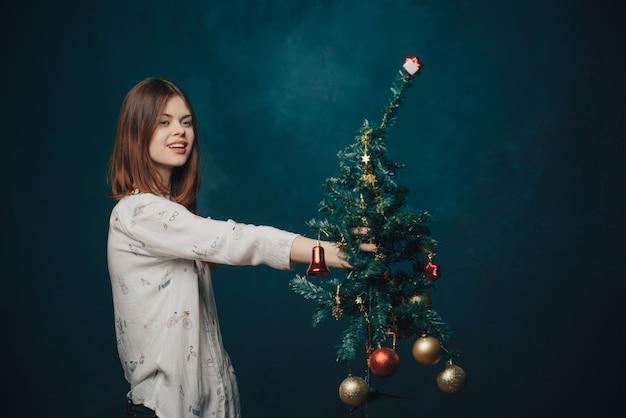 Kobieta z choinką w ręce na niebieskim tle czerwone kulki dekoracji