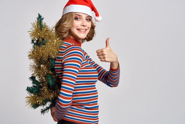 Kobieta z choinką w ręku żółte świecidełko prezenty czapka świąteczna