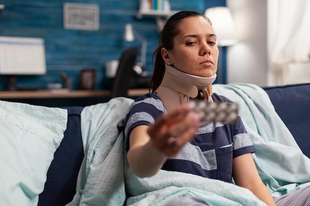 Kobieta z chorobą i kołnierzem z pianki szyjnej na kanapie, przyjmująca leczenie bólu pleców i szyi. dorosły rasy kaukaskiej z przykurczem mięśni po urazie fizycznym w wypadku