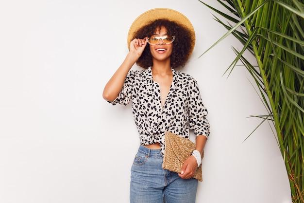 Kobieta z ciemną skórą w cajgach i słomianym kapeluszu pozuje w studiu nad białym tłem z torbą w bali stylu. uspokajający nastrój.