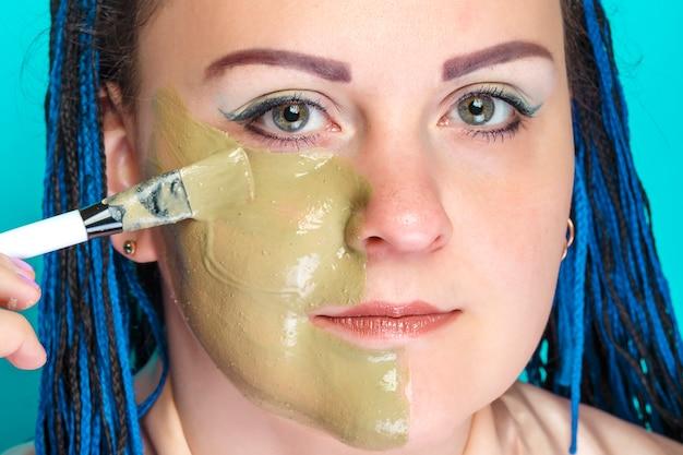 Kobieta z ciemnoniebieskimi warkoczami w stylu afro nakłada pędzelkiem maskę z zielonej glinki na twarz