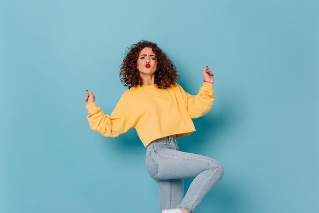Kobieta z ciemnymi kręconymi włosami i jaskrawoczerwoną szminką bawi się i tańczy. migawka młodej dziewczyny w stylowej bluzie i dżinsach na niebieskiej przestrzeni.