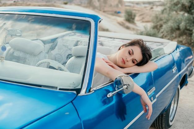 Kobieta z ciemnymi włosami i klasycznym niebieskim kabrioletem w turcji