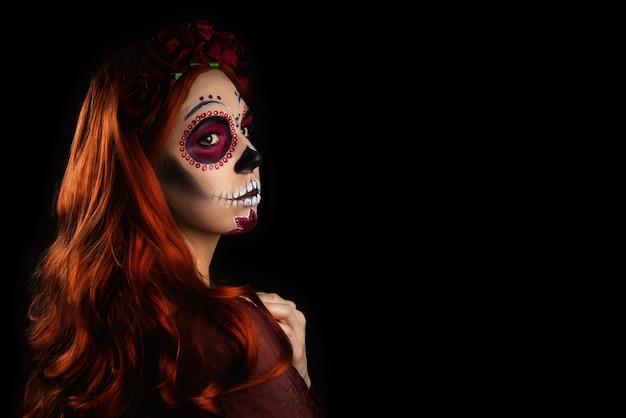 Kobieta z cukru czaszki makijaż i rude włosy na białym tle na czarnym tle.