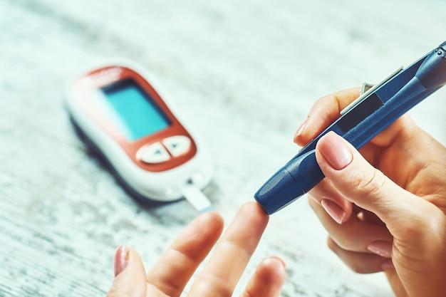 Kobieta z cukrzycą korzystająca z glukometru, kobiece dłonie trzymają glukometr z lancetem na palcu, mierzą poziom cukru, sprawdzają insulinę