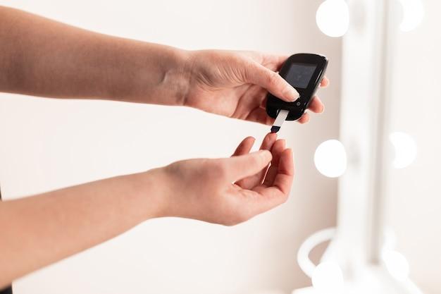 Kobieta z cukrzycą mierzy poziom glukozy we krwi. koncepcja cukrzycy zdrowego stylu życia