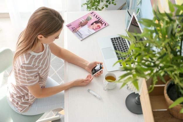 Kobieta z cukrzycą sprawdzająca poziom cukru we krwi w domu
