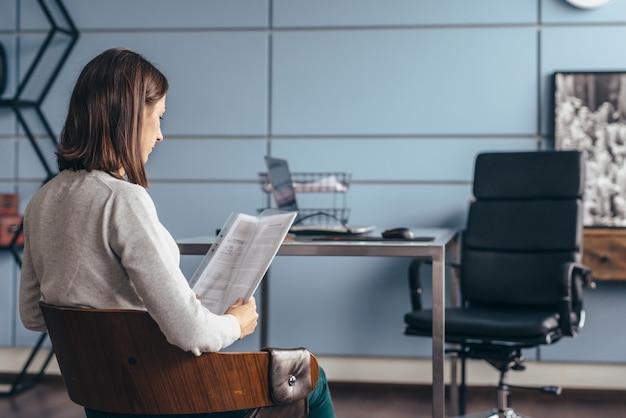 Kobieta z cv siedzi i czeka na rozpoczęcie rozmowy kwalifikacyjnej.