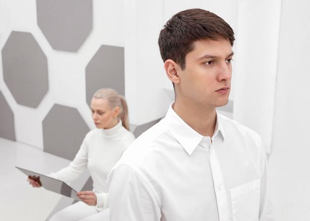 Kobieta z cyfrowym tabletem i mężczyzna z plecami na nią