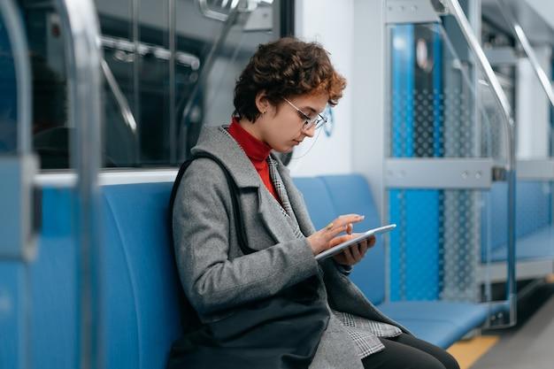 Kobieta z cyfrowym tabletem siedząca w pustym wagonie metra