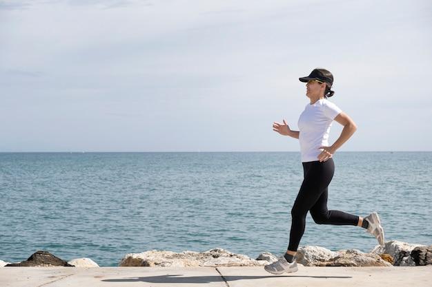 Kobieta z czapką i okularami przeciwsłonecznymi biegnącymi wzdłuż promenady