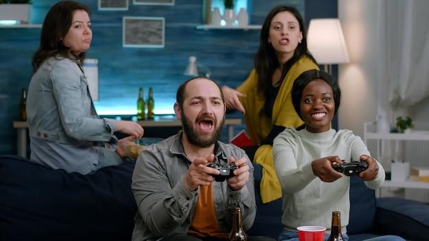 Kobieta z czarną skórą, grając w gry wideo online z przyjaciółmi mężczyzn do rywalizacji w grach za pomocą kontrolera. grupa zwycięskiej gry w wyścigach mieszanych siedząc na kanapie w salonie późno w nocy