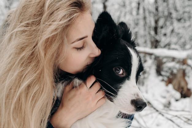 Kobieta z czarno-białym psem rasy border collie w śniegu